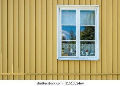 VAXHOLM, SWEDEN - 11 AUGUST, 2018: A window in the wall of a traditional Scandinavian house displays wooden carved ornaments against a lace curtain.