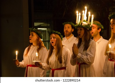 Vaxjo / Sweden - December 13 2016: Students dressed in white and long dresses with candle crown singing songs at Saint Lucia Day, where the Christian martyr is celebrated