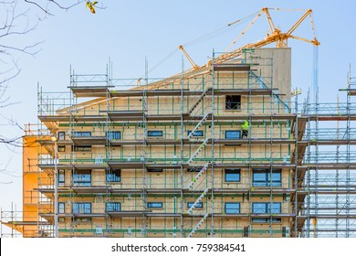 Vaxjo, Sweden - November 13, 2017: Documentary of everyday life and environment. Two workers at a high-rise construction site along street Soderleden with lots of scaffoldings.