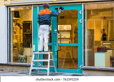 Vaxjo, Sweden - November 13, 2017: Documentary of everyday life and environment. Worker standing on step stool, cleaning up after work outside shop. Person inside looking at him.