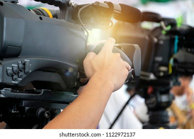 VDO grapher working with professional equipment in movie production. Rear side of Video Cameraman taking photograp to the stage, event and seminar production equipment concept