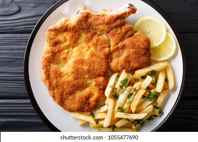 Veal alla Milanese (cotoletta alla milanese) with French fries close-up on a plate on a table. horizontall top view from above
