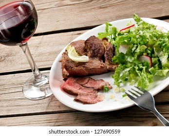 Veal meat with green salad with a red wine glass, horizontal view