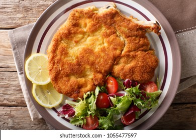 Veal milanese (cotoletta alla milanese) with lemon and fresh vegetable salad close-up on a plate. horizontal top view from above