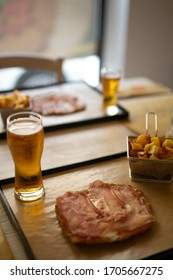Veal milanese (cotoletta alla milanese) with raw ham on top, glass of beer and roasted  potatoes, italian cuisine