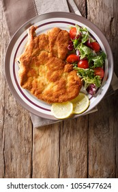 veal Milanese with lemon and fresh salad of tomatoes and lettuce close-up on a plate. Vertical top view from above