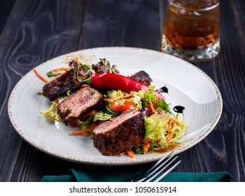Veal salad with lettuce, carrot, tomato and pepper on white plate on dark wooden background, copy space. Restaurant food, close up. Meat salad and glass of whiskey