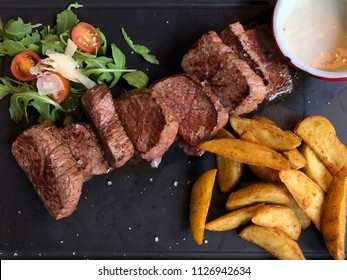 veal slices with salad, french fries and cheese sauce. Tagliatta di manzo