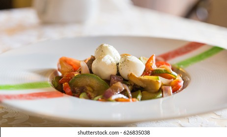 Veal stewed with vegetables and homemade cheese - a dish of Italian cuisine in a restaurant