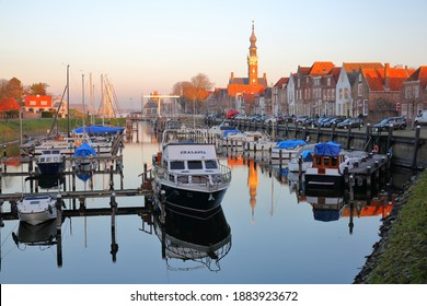 VEERE, NETHERLANDS - DECEMBER 10, 2020: The marina (harbor) and historic buildings with the clock tower of the Stadhuis (town hall) in Veere, Zeeland