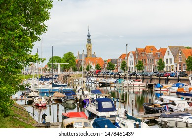 Veere, Netherlands - June 09, 2019: harbor with sailing boats in Veere, with unidentified people. Veere is famous for its picturesque old town and a popular destination for day tripper