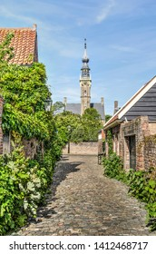 Veere, The Netherlands, May 30, 2019: view through a narrow alley paved with cobble stones and lined with gardens and houses, towards the tower of the town hall