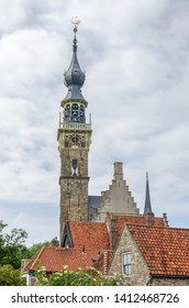 Veere, The Netherlands, May 30, 2019: the tower of the town hall rising above the red tile roofs of the surrounding historic houses