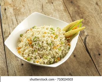 Veg fried frice served in a white bowl on wooden background