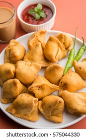 Veg mini Samosa - is a crispy and spicy Indian triangle shape tea time snack. Served with fried green chilly, onion & chutney/ketchup. Over colourful or wooden background. Selective focus