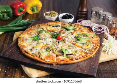veg pizza is made with the combination of delicious vegetables like broccoli, onion, capsicum, carrot, mushroom and cauliflower along with tomatoes and pizza sauce are placed on wooden plate.