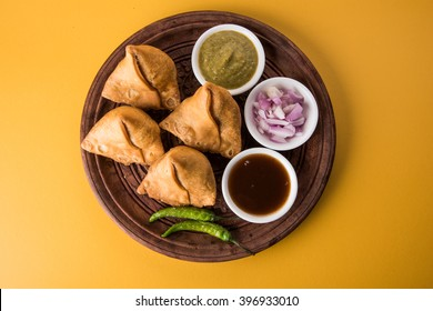 Veg Samosa - is a crispy and spicy Indian triangle shape snack which has crisp outer layer of maida & filling of mashed potato, peas and spices. Served with fried green chilly, onion & chutney/ketchup