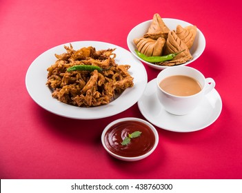 Veg Samosa - is a crispy and spicy Indian triangle shape tea time snack. Served with fried green chilly, onion & chutney/ketchup. Over colourful or wooden background. Selective focus