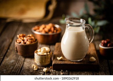 Vegan alternative non dairy milk from nuts in a jug with various nuts on wooden table