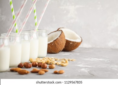 Vegan alternative nut milk in glass bottles on a gray background. Healthy vegan food concept.