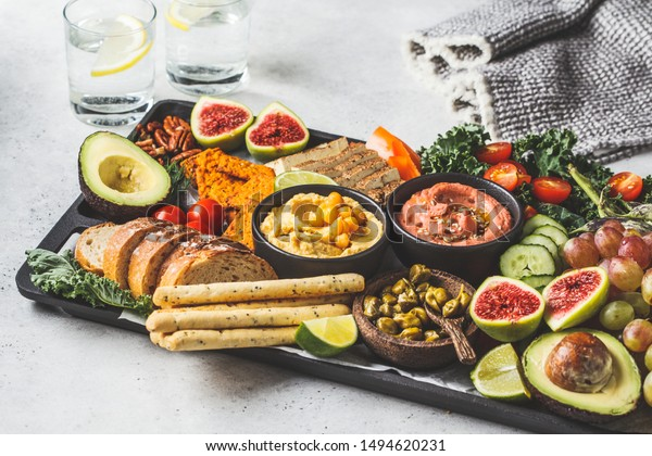 Vegan appetizer platter. Hummus, tofu, vegetables, fruits and bread on a black tray, white background.