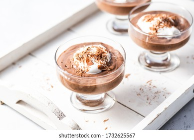 Vegan avocado, banana and cocoa mousse. Topped with  coconut whipped cream and dark chocolate. White background