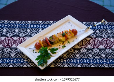 vegan barbecue vegetables on a skewer on a plate on a background of fabric with Asian ornament