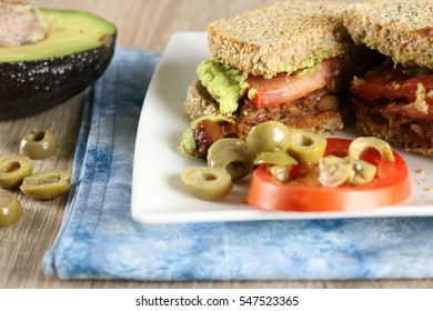 Vegan bean sandwich on whole grain bread with an olives and tomatoes with an avocado off to the side