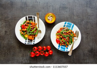 Vegan beans salad with aspargus, micro greens and tomatoes flat lay. Healthy energy boosting salad in plates on dark background. Clean eating, superfood, vegan, detox food concept. Top view