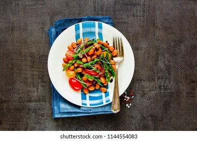 Vegan beans salad flat-lay. Healthy energy boosting salad in plate with aspargus, micro greens and tomatoes on dark background. Clean eating, superfood, vegan, detox food concept. Top view