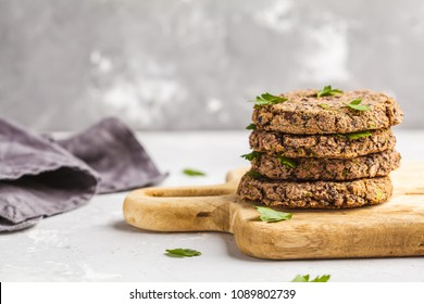 Vegan black bean burgers (cutlets) with parsley on a wooden board.  Healthy vegan food concept.