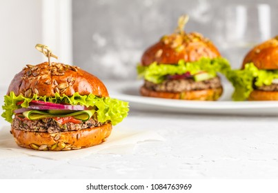 Vegan black bean burgers with vegetables and tomato sauce on white dish, copy space. Healthy vegan food concept.