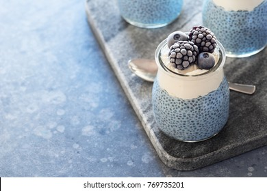 Vegan Blue Spirulina Chia Pudding with Whipped Coconut Cream and Frozen Berries