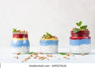 Vegan blue spirulina chia puddings with jam and granola in glass jars on a light blue table. Concept of healthy eating, dieting, fitness menu. Various layered dessert for breakfast.