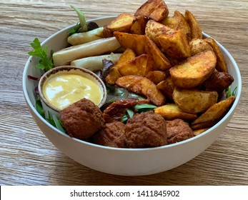 Vegan Bowl with baked potato wedges, white asparagus, radish, green salat and hollandaise sauce on the table close up