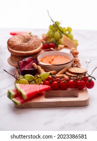 Vegan breakfast board with red pepper hummus, fruits and nuts