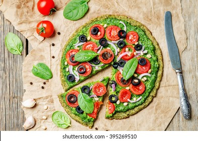 vegan broccoli zucchini pizza crust with spinach pesto, tomatoes, onion and olives. toning. selective focus