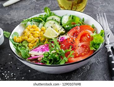 Vegan buddha bowl. Bowl with fresh raw vegetables - cucumber, tomato, watermelon radish, lettuce, arugula and corn. Fresh salad. Vegetarian food.