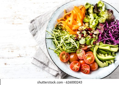 Vegan buddha bowl. Bowl with fresh raw vegetables - cabbage, carrot, zucchini, lettuce, watercress salad, tomatoes cherry and avocado, nuts and pomegranate. White background, top view, copy spae