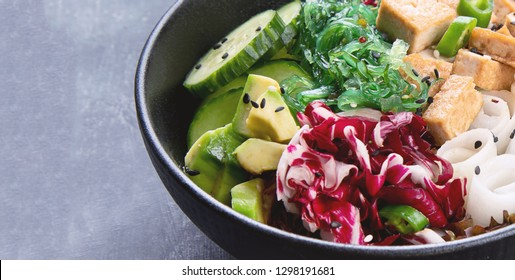 Vegan buddha bowl with guinoa, vegetables and tofu on dark background. Banner