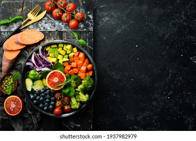 Vegan Buddha Bowl: Sweet Potatoes, Blueberries, Avocados, Cabbage and Orange. Dietary food. Top view. Free space for your text.