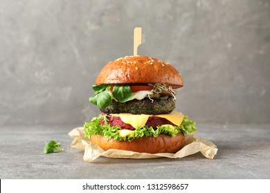 Vegan burger with beet and falafel patties on table