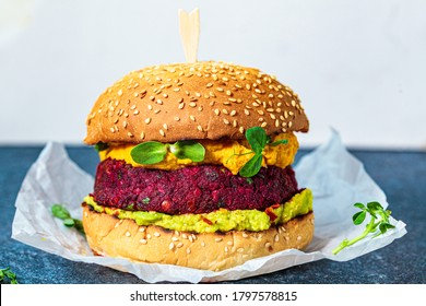 Vegan burger with beetroot cutlet, sweet potato sauce and guacamole.