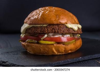 Vegan burger. Falafel and craft bun on a stone tray.