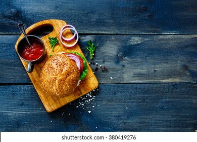 Vegan burger with fresh vegetables on dark  rustic wooden table, top view, border. Healthy fast food background with space for text.