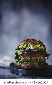 Vegan burger with fresh vegetables on dark rustic wooden table,