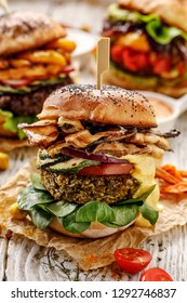 Vegan burger, green peas burger, homemade burger with green peas cutlet, grilled mushrooms, zucchini,  tomato, red onion, lamb's lettuce, and curry sauce on a wooden background. Healthy eating concept