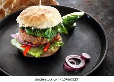 Vegan burger. Burger with vegetable cutlet and vegetables served on a black plate
