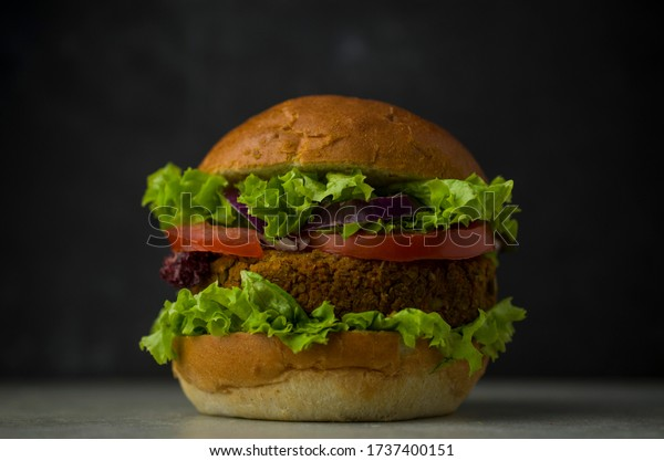Vegan burger with vegetables on table