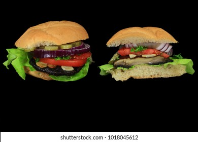 Vegan Burgers from grilled cap Organic Portobello mushroom, Lettuce, slices tomato, red onion, pickle, fried garlic, parsley in whole wheat hamburger bun, entire and cut on half on black background